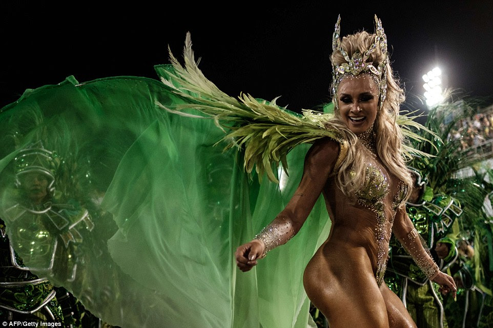 A woman from the Unidos da Tijuca samba school dances in little more than a pair of fabric wings and a bikini