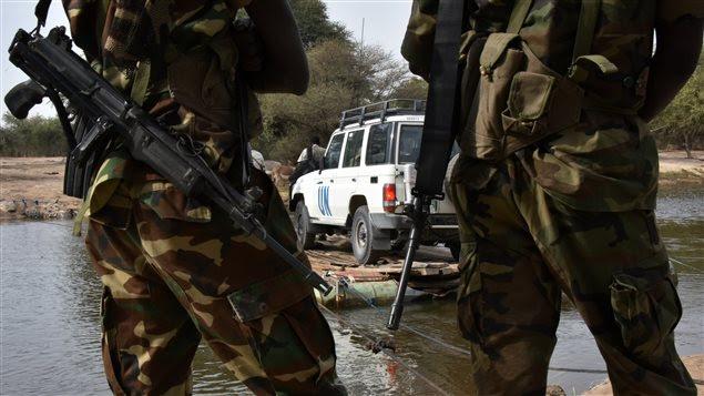 Des soldats tchadiens regardent un véhicule d'un convoi des Nations unies se dirigeant vers un camp de réfugiés ayant fui le Nigeria et les attaques de Boko Haram.