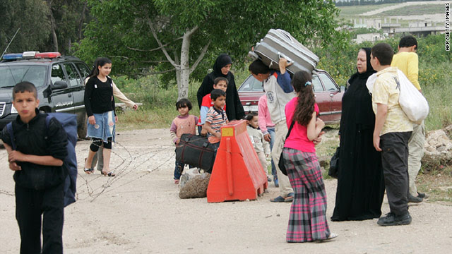 Syrians flee on foot on April 28, 2011 into Wadi Khaled in Lebanon after unrest broke out in the Syrian town of Tall Kalakh.