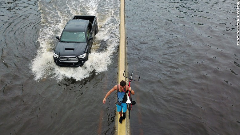 """A man walks on a highway divider while carrying his bicycle through San Juan, Puerto Rico, on Thursday, September 21. Hurricane Maria <a href=""""http://www.cnn.com/interactive/2017/09/world/hurricane-maria-puerto-rico-cnnphotos/index.html"""" target=""""_blank"""">left the island without power</a> after making landfall as a Category 4 storm."""