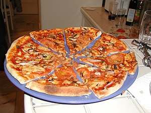 A pizza with tomato sauce, cheese, tomatos, fi...