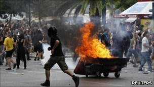 Protesters run away from tear gas canister and a burning barricade during clashes with riot police in Athens' central Syntagma (Constitution) Square, 15 June 2011