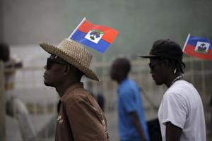 Two protesters carriying Haitian flags on his heads march during a demonstration against the electoral process in Port-au-Prince, Haiti