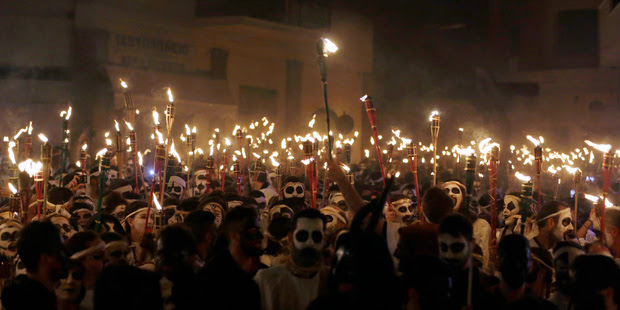 Young men and women with faces painted to resemble black-and-white masks take part in the Torch Parade on the island of Naxos, Greece. Photo / AP