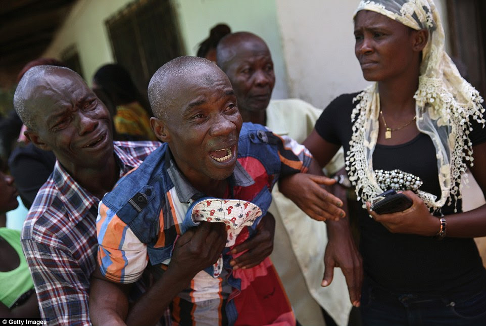 Beyond pain: In this image, Varney Jonson, 46, is seen crying out in pain as crews - donning white overalls, gloves and goggles - transport the body of his wife, Nama Fambule, to a crematorium following a year-long illness that he insists was not Ebola-related