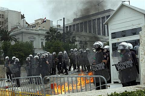 Riot police stand guard against workers and youth in Greece who are protesting the imposition of austerity measures inside the country. Europe is suffering from the world capitalist crisis. by Pan-African News Wire File Photos