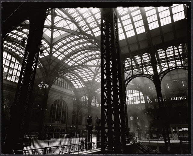 Penn Station, Interior, Manhattan. Massive steel uprights in the center and to the left, with lighter steel tracery and windows above; men stand near stairway to trains.