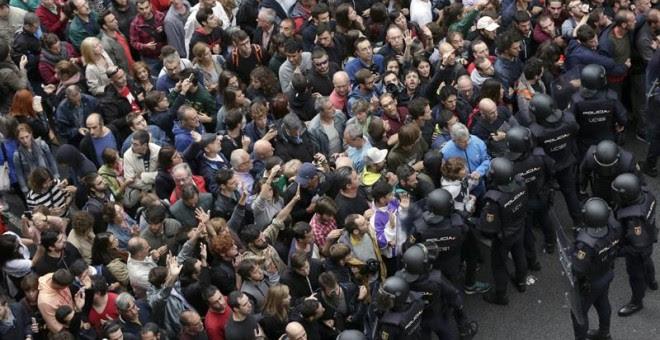 Policía Nacional y Guardia Civil ante los concentrados en el colegio Ramón Llull de Barcelona./ EFE
