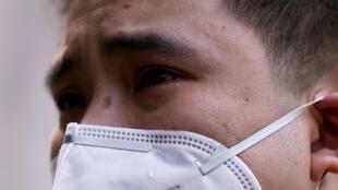 武汉一名戴口罩男子2020年4月4日悼念新冠病毒死者哭泣默哀。