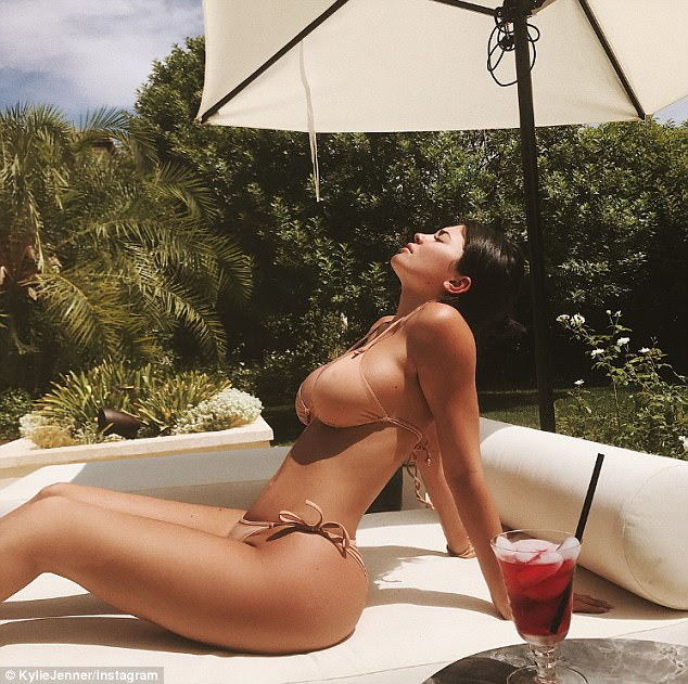 Bikini babe:Kylie Jenner toasted her latest business achievement by posing for a series of seriously sexy swimsuit shots on Wednesday afternoon