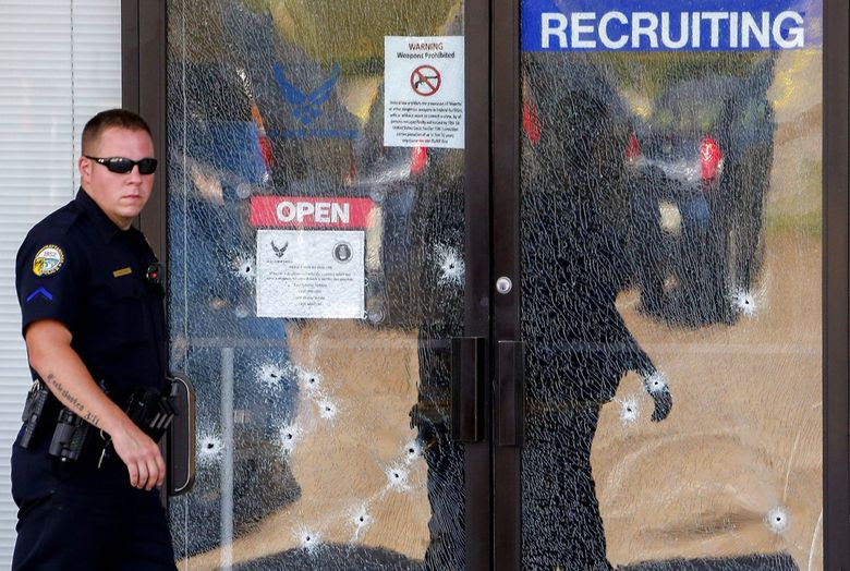 A Chattanooga Police officer walks past the bullet-riddled front door of a military recruiting office after a deadly shooting in Chattanooga, Tenn. (Erik S. Lesser / European Pressphoto Agency)