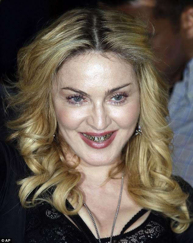 Madonna shows off her rather distinctive grills as she visits the Rome branch pf her hard Candy fitness studio empire on Wednesday