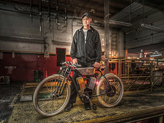 Ianis Vasilatos shows off his Local Motors Cruiser, a motorized bike made using a 3-D printer. Photo by Jerry Ferguson, courtesy of Local Motors. Click to enlarge.
