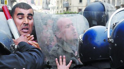 UNA ARREMETIDA. UN GRUPO DE MANIFESTANTES EN ARGELIA TRATAN DE AVANZAR, AYER,  SOBRE UN RETEN POLICIAL DURANTE UNA MARCHA EN LA CAPITAL.