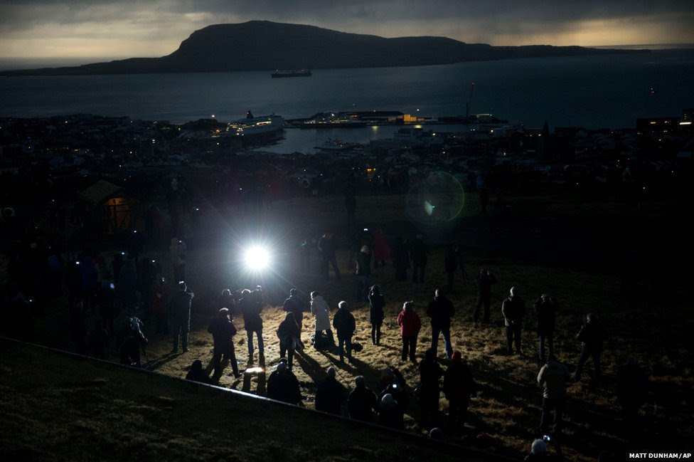 People watch in darkness during the totality of a solar eclipse in Torshavn in the Faroe Islands