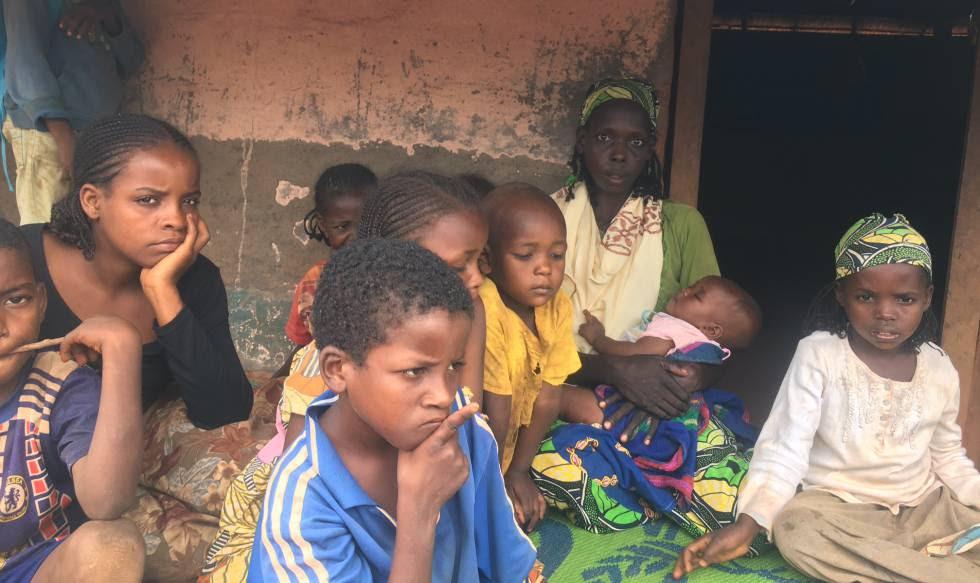 Ousman Kaltoumi, con uno de sus hijos en brazos, ante la cabaña en la que vive en el campo de Timangolo (Camerún).