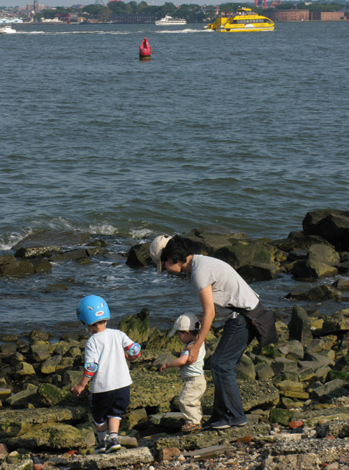 a kid wears a helmet on the shore of the Hudson River
