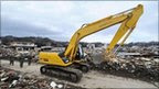 A worker operates the excavator during a clean-up operation in Tarou, north of Morika in Iwate prefecture
