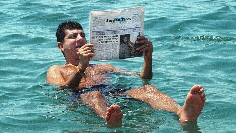 A man reads a newspapers while floating in the Dead Sea, southwest of Amman - 31 August 1999