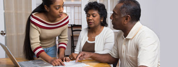 Photo: Woman discussing financial documents with senior parents