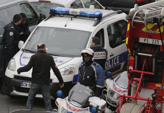 Policemen work at the scene after a shooting at the Paris offices of Charlie Hebdo, a satirical newspaper, January 7, 2015.  REUTERS-Christian Hartmann