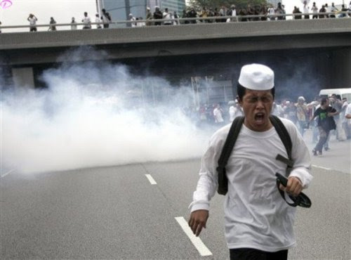 A protester runs away from tear gas fired by Malaysian riot police during a protest against  the use of English to teach math and science in Kuala Lumpur, Malaysia, Saturday, March 7, 2009.AP Photo
