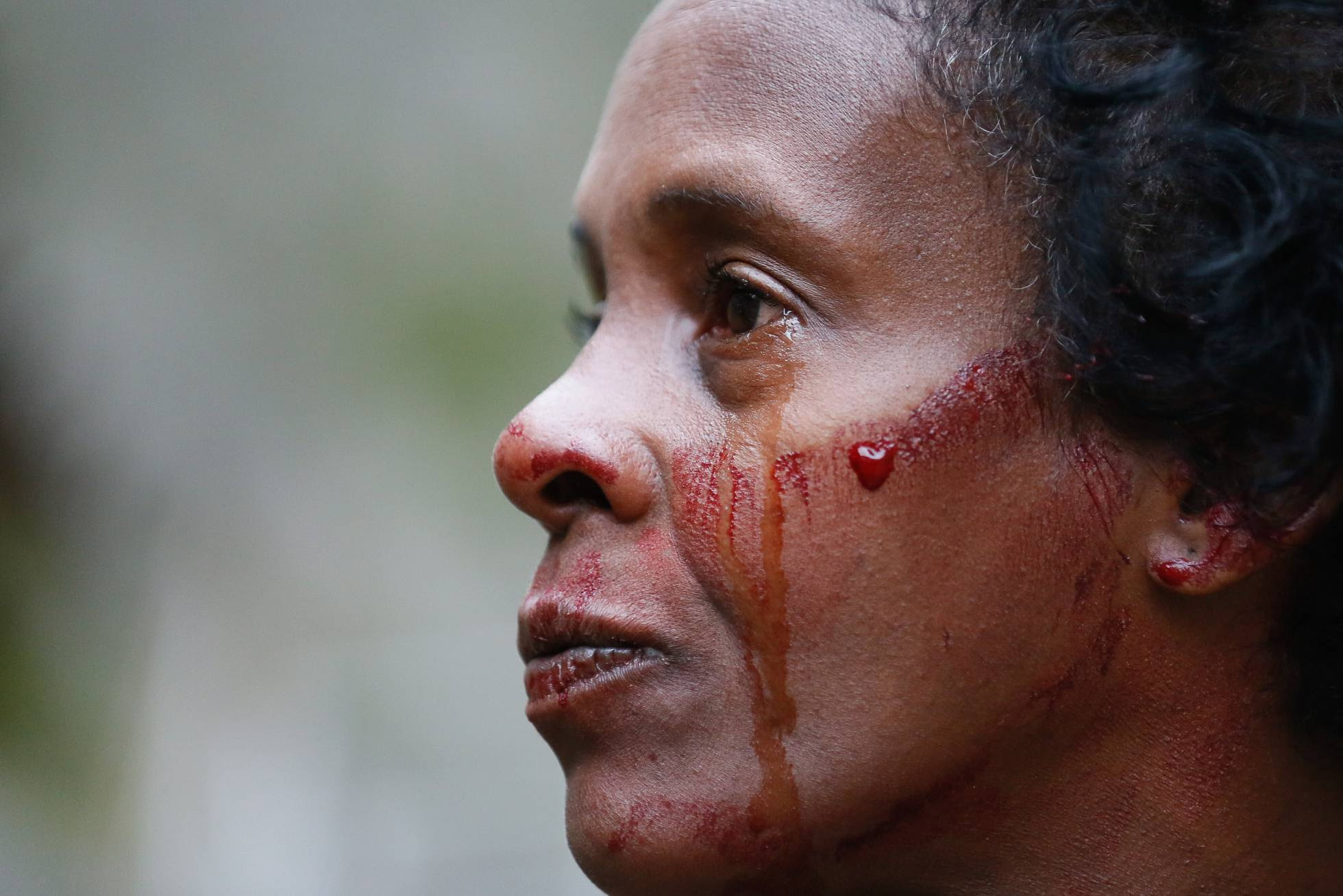 Sheila Cristina Nogueira da Silva chora a morte do filho Carlos Eduardo, 20 anos, com seu sangue no rosto, no dia 10 de junho, no Rio de Janeiro.