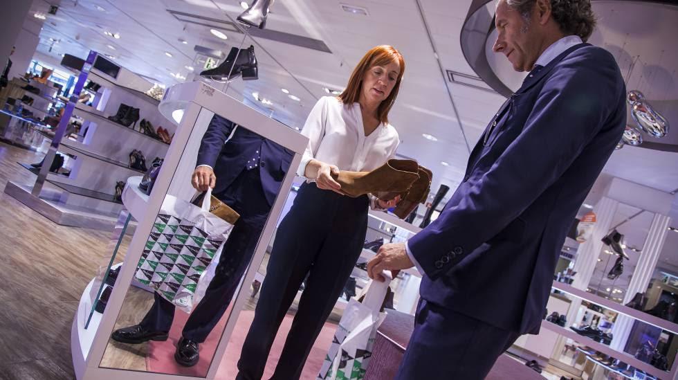 Un cliente con una bolsa de plástico y una vendedora en la sección de calzado de El Corte Inglés de Castellana en Madrid