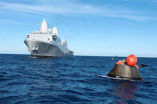 The USS Anchorage approaches the Orion EFT-1 spacecraft in preparation for the capsule being towed back to the ship for securing aboard the vessel, on December 5, 2014.