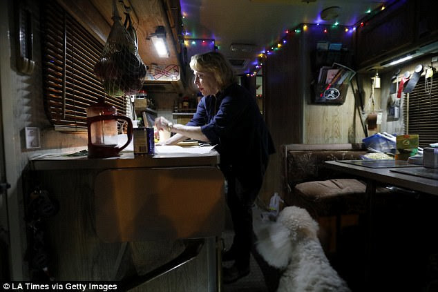 Kathy, 65, feeds her aging Standard Poodle in her RV in a parking lot in Santa Barbara. She says she spent her career working as a paralegal and was a homeowner until 2013