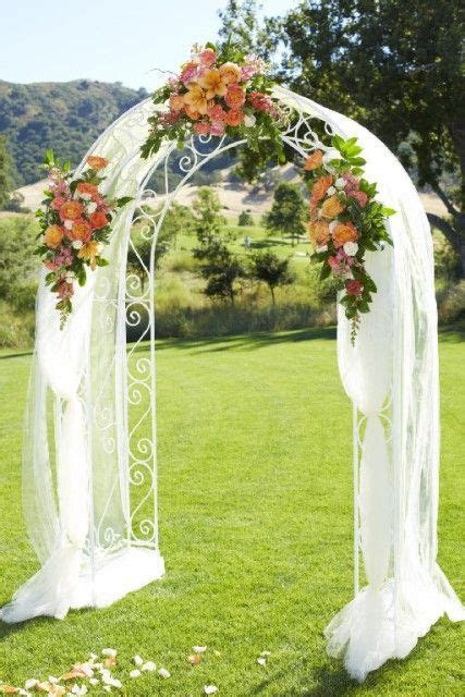 A golf course wedding arch with tulle draping and orange