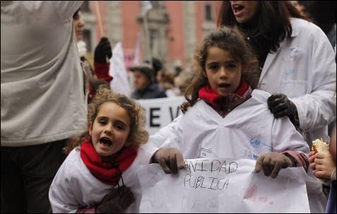 Dos niñas y su madre protestan contra la privatización de la sanidad pública.