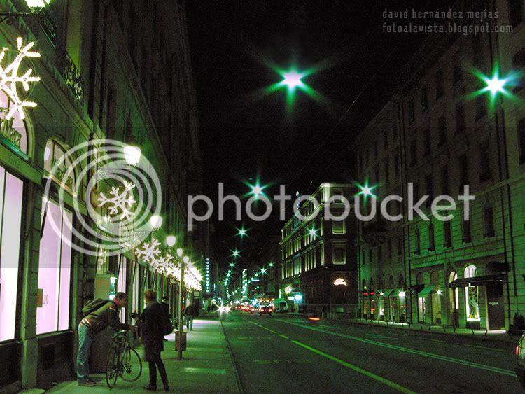 Calle de Ginebra iluminada por la noche en Navidad con una pareja en bicicleta que espera el autobús