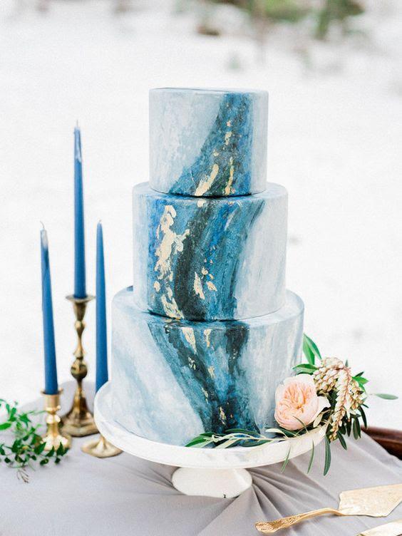 eine indigo-und gold-Blatt-Hochzeits-Kuchen und indigo Kerzen für einen Akzent