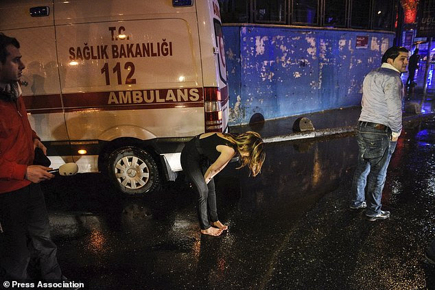 A woman reacts next to an ambulance