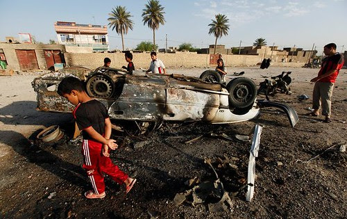 Youth walking around area where car bombs exploded in attacks on Iraq security forces. The security apparatus was established and trained by the United States occupation forces which ostensibly withdrew in six months before. by Pan-African News Wire File Photos