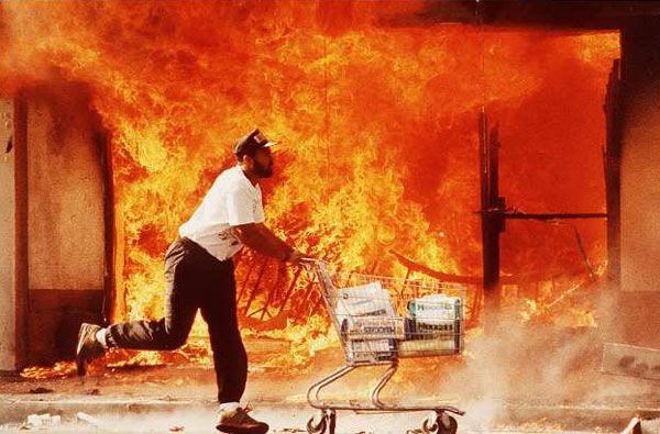 A man runs off with a shopping cart full of looted items during the 1992 Los Angeles riots.