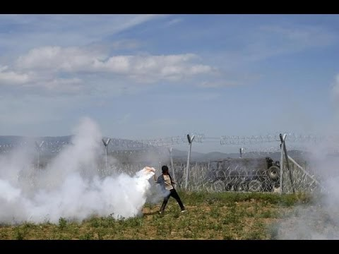 Mazedonischer Polizist und Flüchtling mit Smaltalk am Grenzzaun