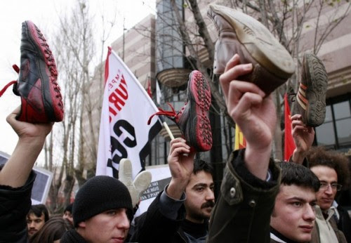 Leftist protesters display shoes as they protest in front of the U.S. Embassy in Ankara December 18, 2008. Turkey's Communist Party members organized the rally to protest against the U.S. and to support Iraqi journalist Muntazer al-Zaidi, who hurled his shoes at U.S. President George W. Bush during a news conference in Iraq on December 14, 2008. REUTERS/Umit Bektas (TURKEY)