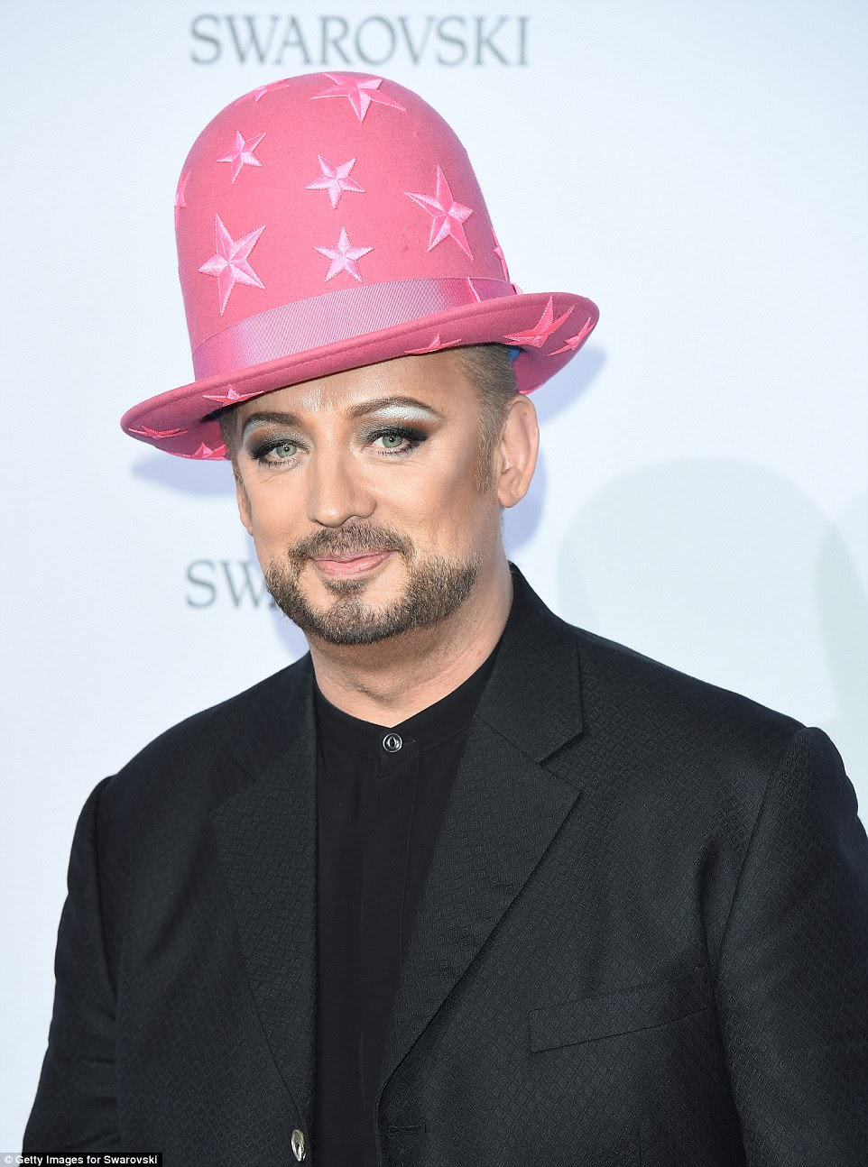 Hats off to him: Boy George rocked his trademark wacky headgear, this time opting for a print star-print trilby
