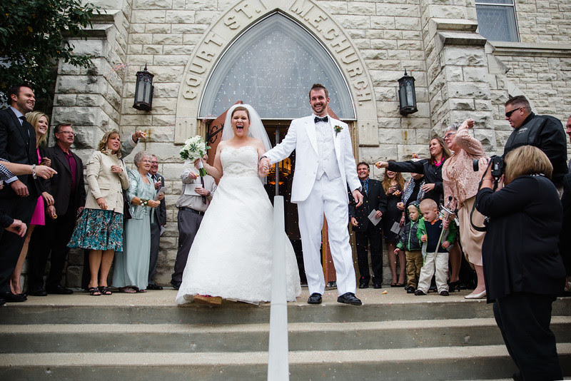 The bride and groom exit the church with their guests throwing ice cream sprinkles at them at Court Street United Methodist Church in downtown Rockford Illinois for an Autumn wedding.