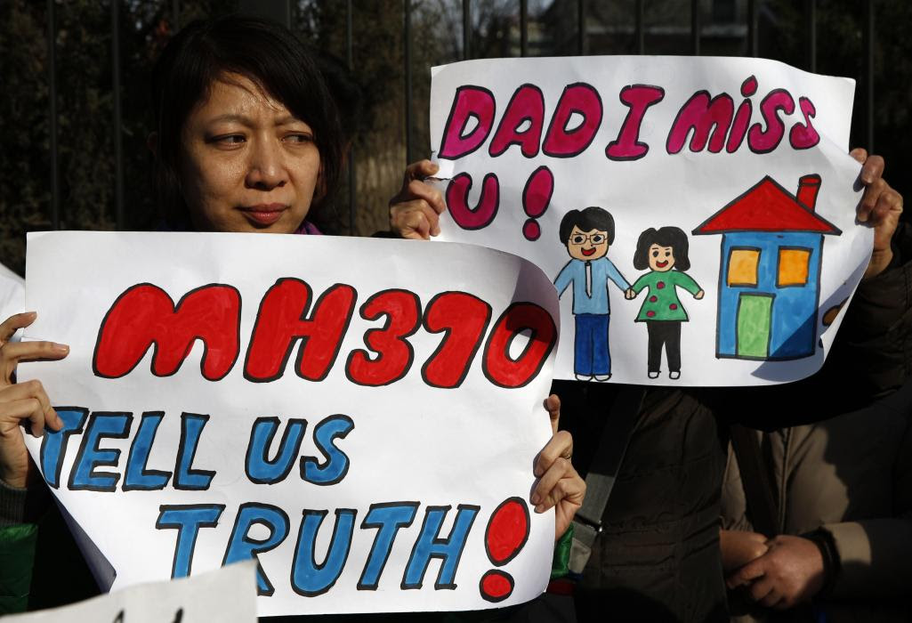 Catherine Gang, whose husband Li Zhi was onboard the missing Malaysia Airlines flight MH370, holds a sign during a gathering outside the Malaysian...