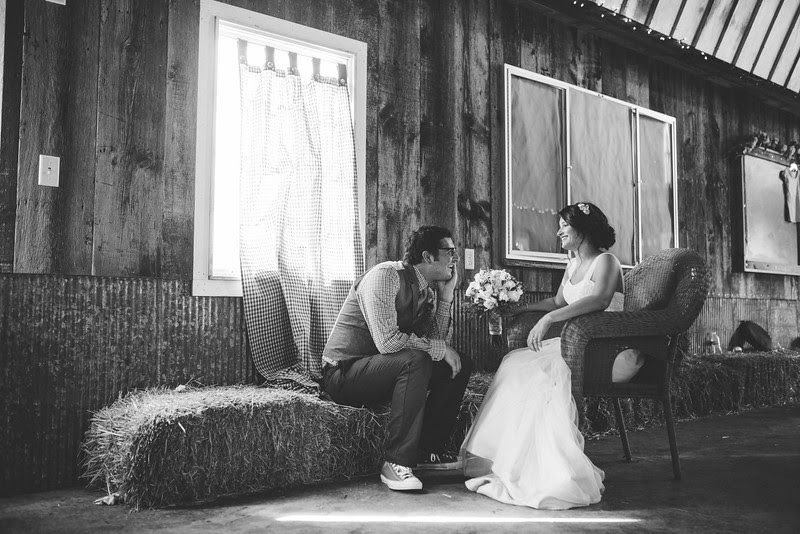 Bride and groom share a quiet moment trying to decide about rain fall at Busy Barns Adventure farms before a wedding ceremony at Busy Barns Adventure Farms in Fort Atkinson Wisconsin about 30 minutes east of Madison and an hour north of Chicago. Photo by Mindy Joy Photography.