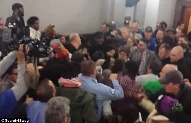 Fracas: A mass brawl breaks out at a meeting at St Louis City Hall when tensions boil over during a discussion on a proposed new law that would see civilians examining the future conduct of police
