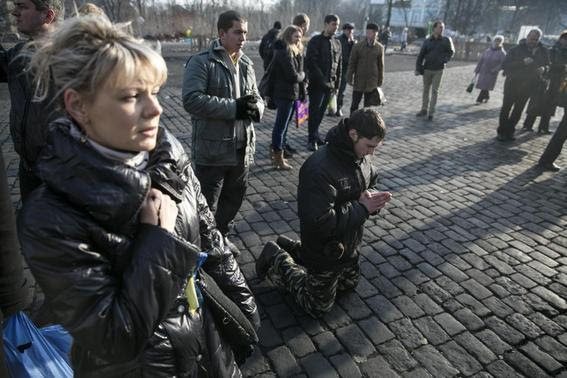 A man kneels as he pays his respects to fallen anti-Yanukovich protesters near Kiev's Independence Square February 24, 2014. REUTERS-Baz Ratner