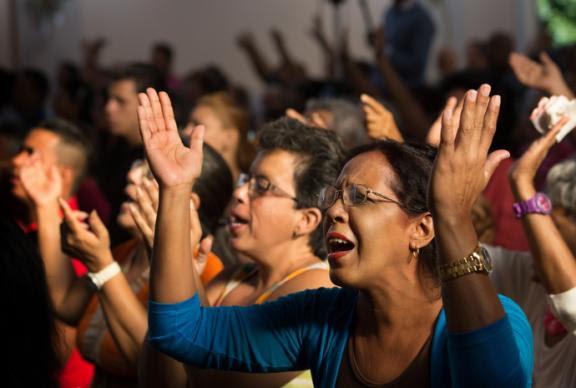 Parishioners raise their arms in praise during worship at Vedado Methodist Church in Havana. Photo by Mike DuBose, UMNS.