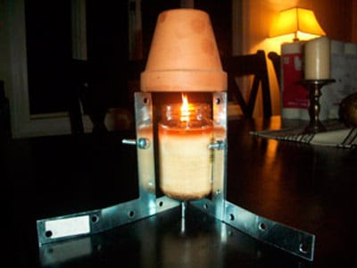 calentador hecho con una base metalica y tres jarrones de barro