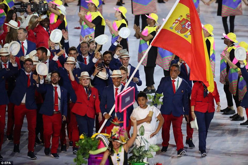 O time espanhol, vestindo vermelho e marinha ternos e chapéus brancos, foram levados através do estádio por Rafael Nadal