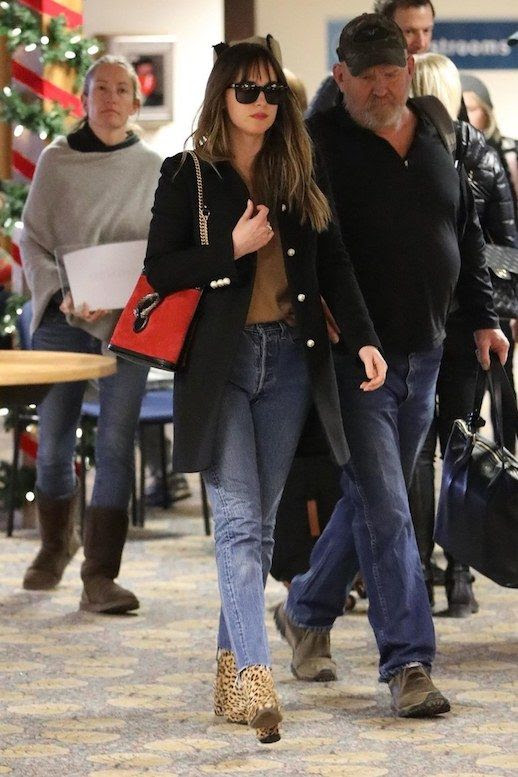 Le Fashion Blog Dakota Johnson Airport Style Gucci Coat Tan Sweater Vintage Jeans Leopard Print Booties Via Vogue
