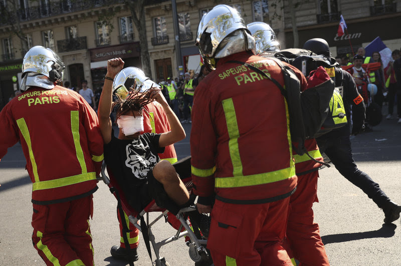 An injured man is carried away by emergency personnel during a yellow vest demonstration in Paris, Saturday, April 20, 2019. French yellow vest protesters are marching anew to remind the government that rebuilding the fire-ravaged Notre Dame Cathedral isn't the only problem the nation needs to solve. (AP Photo/Francisco Seco)